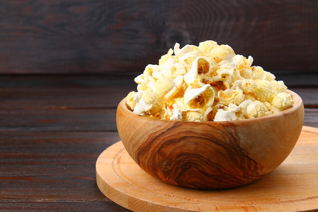 Salted popcorn in a wooden bowl on a wooden table