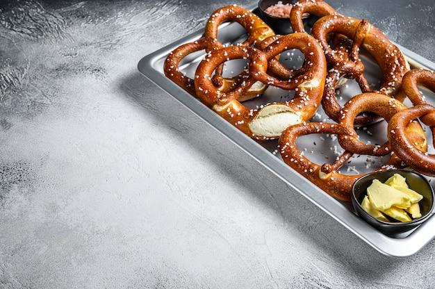 キッチンのベーキングパンに海塩を入れたプレッツェルを塩漬けにしました。白色の背景。上面図。スペースをコピーします。