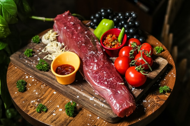 Salted raw meat on the wooden board with vegetables mushrooms bell pepper tomato sauce side view