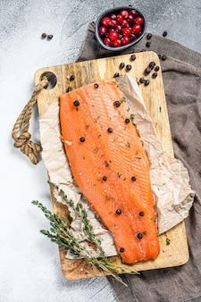 ハーブとスパイスを木製のまな板に塩漬けのサケの切り身。灰色の表面。上面図