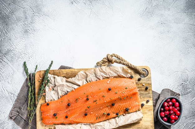 Salted salmon fillet on a wooden cutting board with herbs and spices. gray background. .