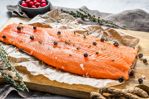 Salted salmon fillet on a wooden cutting board with herbs and spices.