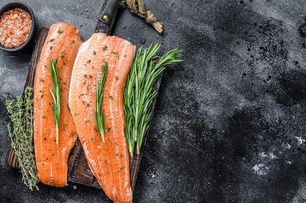 Филе морской рыбы малосольного лосося или форели со специями и зеленью. черный деревянный стол. вид сверху.