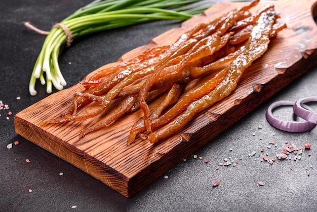Нарезанная дольками соленая копченая рыба на закуску к пиву. закуски из сушеной рыбы