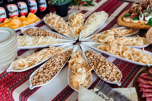 Salted snacks lie in long white dishes