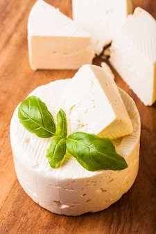 Соленый мягкий сыр с листом базилика на доске