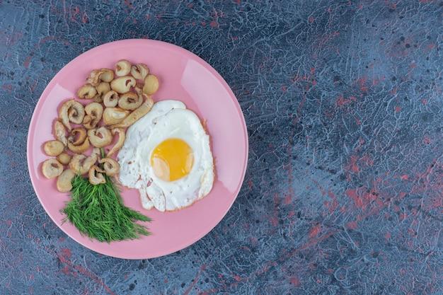 Uovo fritto salato e speziato con prezzemolo su un piatto rosa.