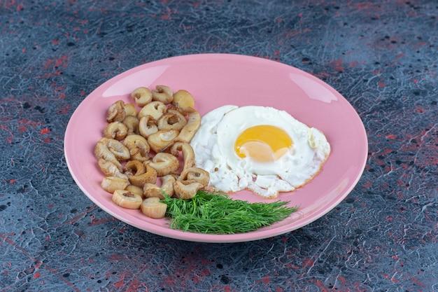 Uovo fritto salato e speziato con prezzemolo su un piatto rosa