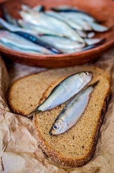 Соленая килька в миске и черный хлеб