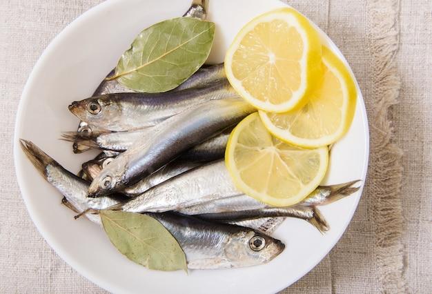 Килька соленая со специями и лимоном на белой тарелке. скатерть грубая. крупным планом вид сверху