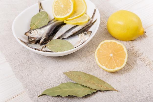 Килька соленая со специями и лимоном на белой тарелке. скатерть грубая.