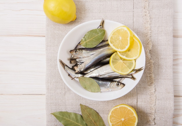 Килька соленая со специями и лимоном на белой тарелке. деревянный стол с грубой скатертью.