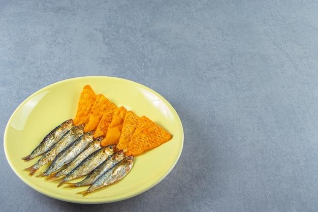 Соленые шпроты и чипсы на тарелке рядом с бокалом пива, гренками и семенами, на мраморном фоне.