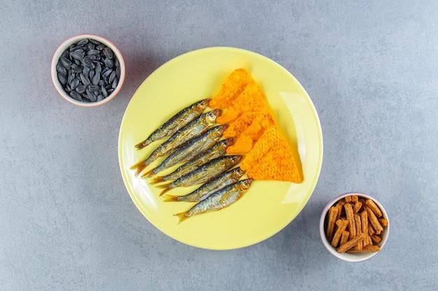 Соленые шпроты и чипсы на тарелке рядом с бокалом пива, гренками и семенами на мраморной поверхности.