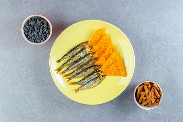 Salted sprats and chips on a plate next to glass of beer, croutons and seed , on the marble surface.