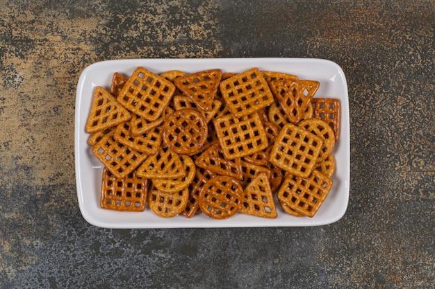 Vari cracker salati sul piatto bianco.
