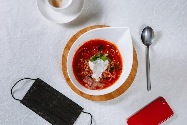 Солянка в блюде на столе ресторана. рядом с едой телефон, медицинская маска.