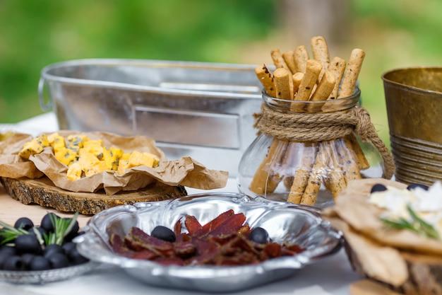 Солено-сырный батончик из нескольких видов сыра, винограда, оливок и закусок, украшенный на старинном деревянном столе