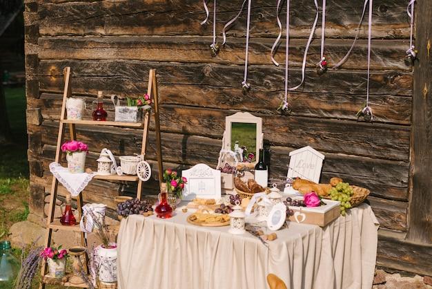 塩辛いバー。お祝い。チーズバー。湾曲した金属製の脚を持つヴィンテージの木製のテーブルに飾られたいくつかの種類のチーズ、ブドウ、オリーブ、パンのチーズバー