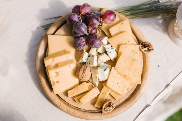 Salty bar. celebration. cheese bar. cheese bar of several kinds of cheese, grapes, olives and bread decorated on vintage wooden table with curved metal legs, table standing on a green lawn