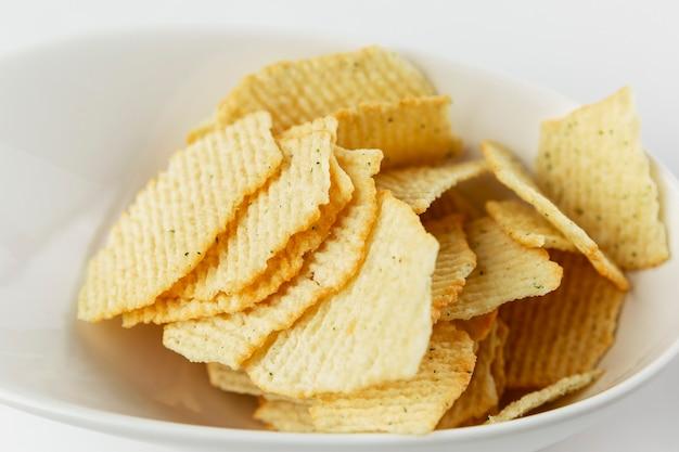 プレートの塩辛いチップス。食欲をそそるスナック。閉じる。