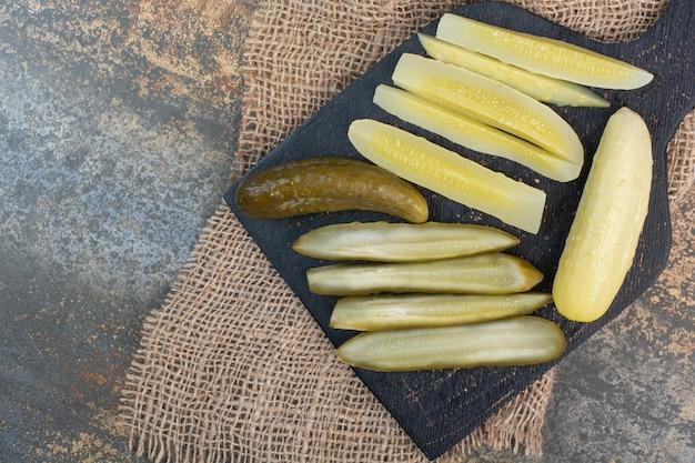 Соленые вкусные огурцы на темной доске. фото высокого качества