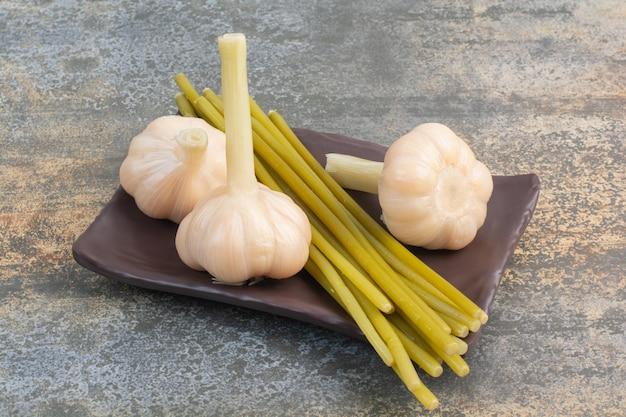 대리석 바탕에 긴 녹색 야채와 함께 짠 맛있는 마늘. 고품질 사진 무료 사진