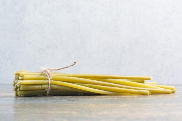 白い背景の上のロープで塩辛いおいしい野菜
