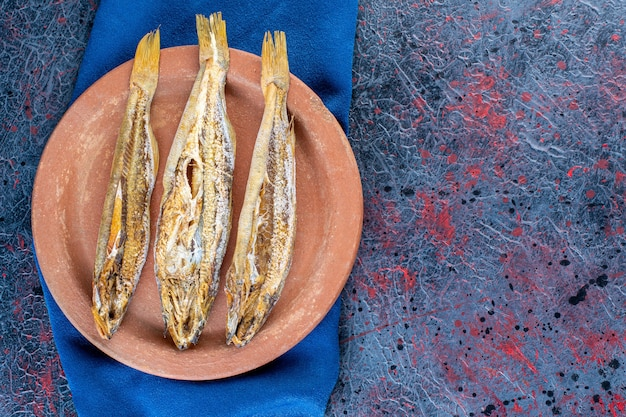 Соленая вяленая рыба, изолированные на глиняной тарелке на темной поверхности