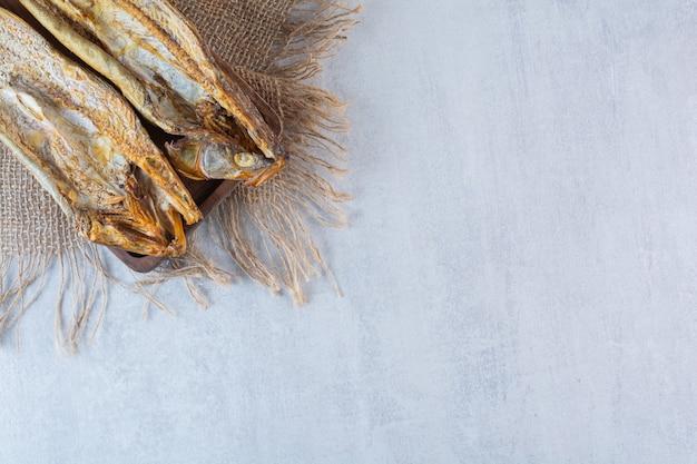 Pesce essiccato salato isolato su una tavola di legno.