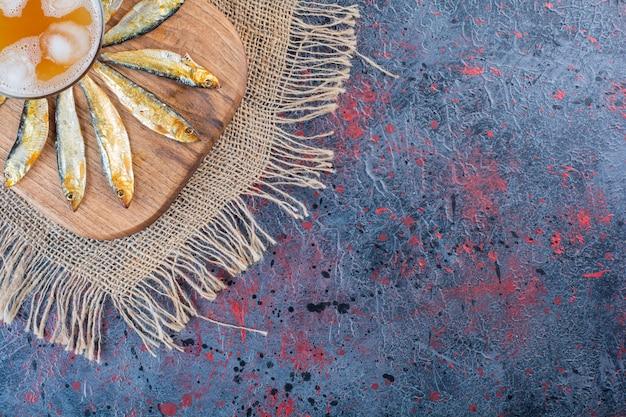Pesce essiccato salato con un boccale di birra di vetro isolato su una tavola di legno.