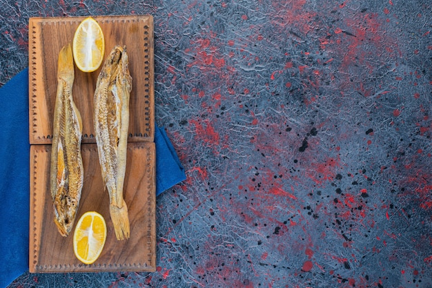 Salty dried fish with a slice of lemon isolated on a wooden board