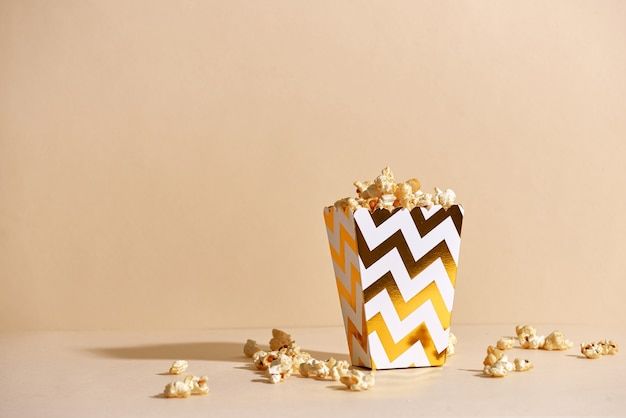 ファッションの表面に金色の紙コップで塩辛い新鮮な無愛想な自家製ポップコーン