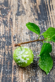 Salty green plum with branch high angle view on a wooden wall