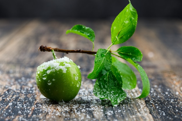 Salty green plum with branch side view on wooden and dark wall
