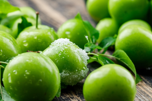 Salty green plums with leaves on wooden wall, close-up.