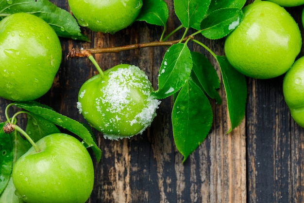 Salty green plums with leaves on wooden wall, flat lay.
