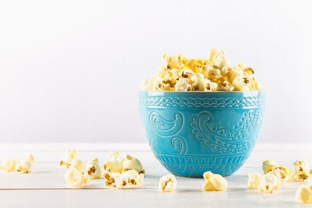 Salty popcorn in a blue cup is on a wooden table. popcorn lies around the bowl.