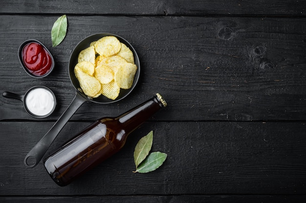 Salty potato chips snack and bottle of beer on black wooden