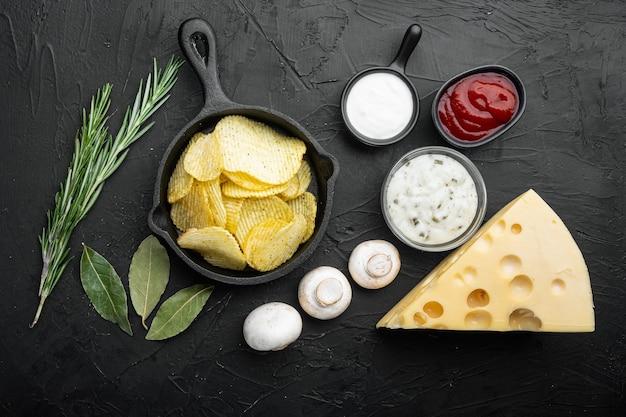 塩味のポテトチップススナックセットチーズとオニオン、サワークリーム、黒い石のテーブル、上面図フラットレイ