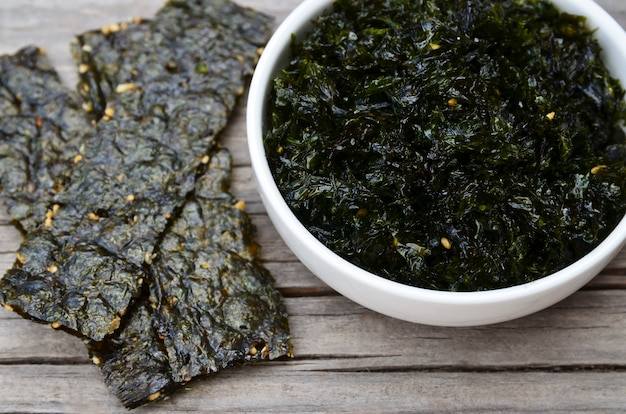 Salty roasted dried seaweed nori with sesame seeds in a white bowl
