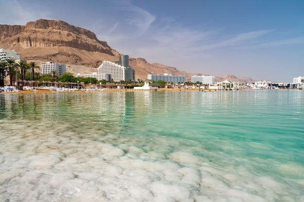 Соленый берег мертвого моря на фоне небольшого курортного городка в израиле. красивый городской пейзаж. в бирюзовой воде отражаются высокие небоскребы.