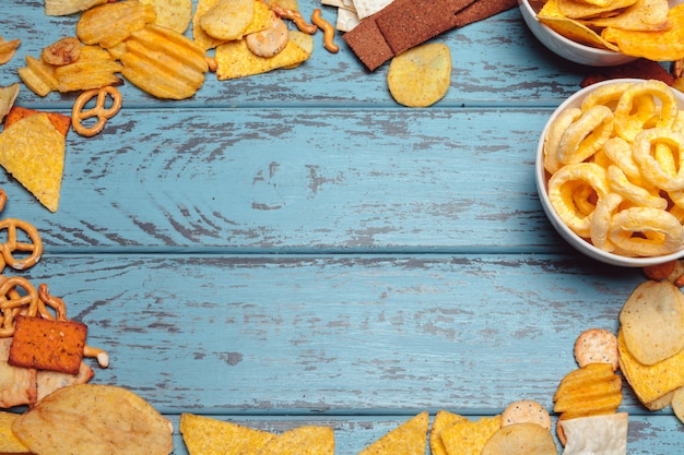 Salty snacks frame with pretzels, chips, crackers on wooden surface