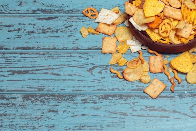 塩味のスナック。プレッツェル、チップ、木製テーブルの上のクラッカー。不健康な製品