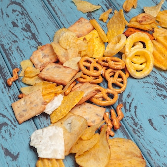 Salty snacks. pretzels, chips, crackers on wooden . unhealthy products