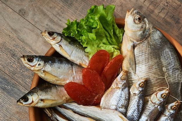 Соленая вяленая рыба на деревянном столе. радужная корюшка, лещ обыкновенный, вобла, шемай, икра макрурус и листья салата.