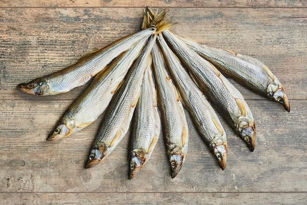 Соленая вяленая рыба на деревянном столе. радужный корюшка (osmerus mordax)
