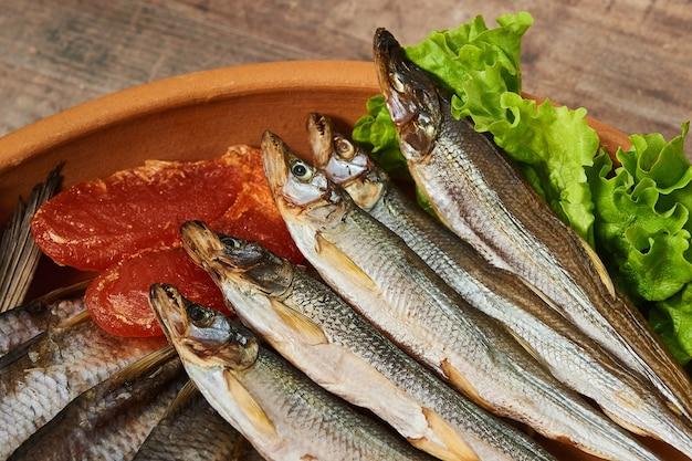 Соленая вяленая рыба на деревянном столе. радужная корюшка, икра вобла, макрурус и листья салата.