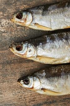 Соленая вяленая рыба на деревянном столе. шемай (chalcalburnus)