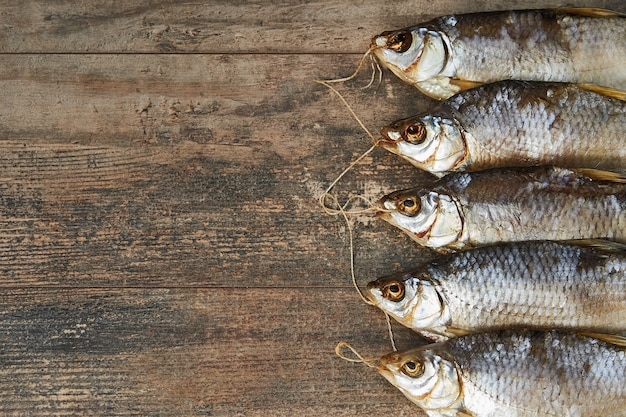 Соленая вяленая рыба на деревянном столе. вобла (rutilus caspicus)